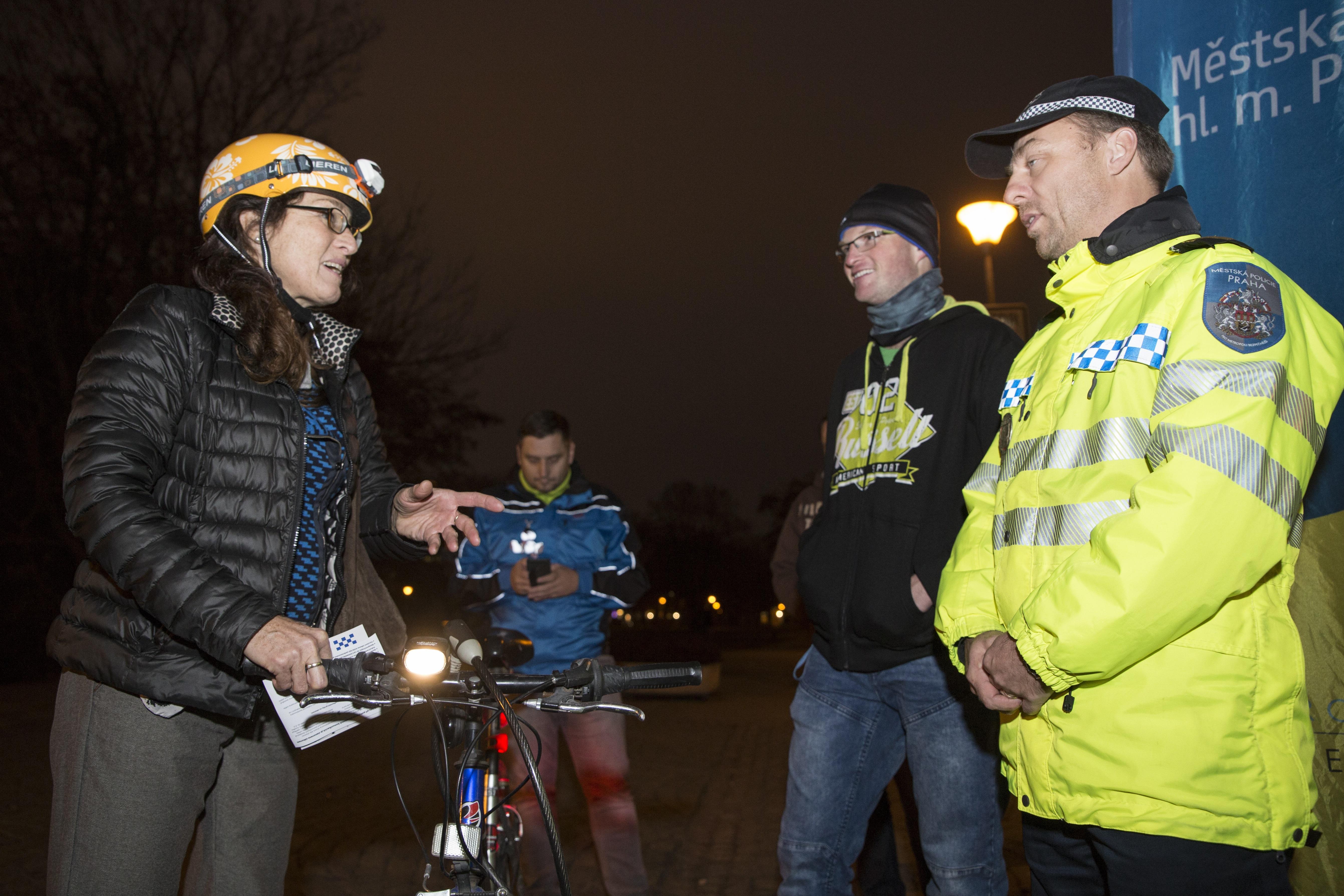 cyklistka se zapnutýmsvětlem se baví s policistou