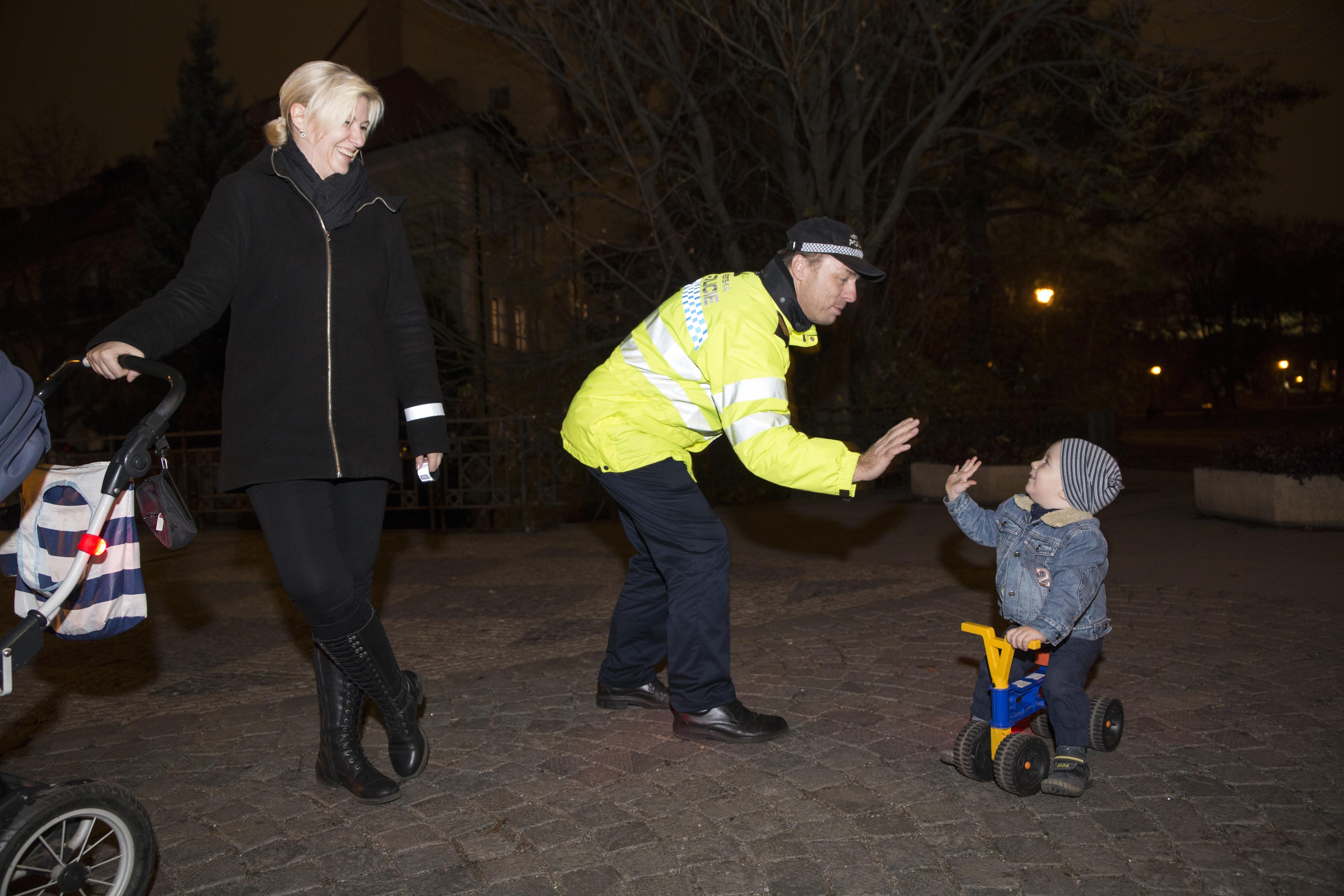 policista si plácá rukou s dítětem na šlapadle